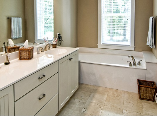 remodeled bathroom with corner fixture tub and his-and-hers sinks